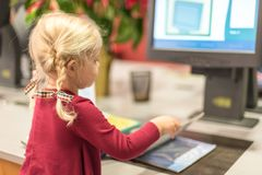 Young girl checking out library books by herself at the automate. Young preschool aged girl using technology to check out library books by herself at the Royalty Free Stock Image