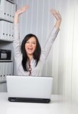 Young girl cheering on a computer. Young woman raises her arms jubilantly on the computer Stock Photo