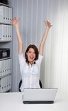 Young girl cheering on a computer. Young woman raises her arms jubilantly on the computer Stock Images