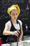 Young girl in a chef`s hat cooks in a large saucepan in a black. Young girl in a chef`s hat cooks in a large saucepan in black kitchen Stock Photo