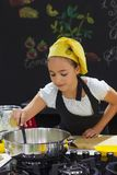 Young girl in a chef`s hat cooks in a large saucepan in a black. Young girl in a chef`s hat cooks in a large saucepan in black kitchen Stock Images