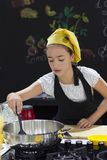 Young girl in a chef`s hat cooks in a large saucepan in a black. Young girl in a chef`s hat cooks in a large saucepan in black kitchen Stock Photography