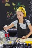 Young girl in a chef`s hat cooks in a large saucepan in a black. Young girl in a chef`s hat cooks in a large saucepan in black kitchen Royalty Free Stock Photography