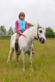 Young girl child sitting astride a white horse Stock Photography