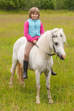 Young girl child sitting astride a white horse. And smiling Stock Images