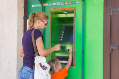 A young girl with the child to withdraw money from the ATM Sberbank. Anapa, Russia - September 20, 2015: A young girl with the child to withdraw money from the Royalty Free Stock Image