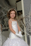 Young girl child at a wedding near the mirror. Young girl child at a wedding in a white dress royalty free stock images