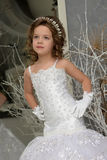 Young girl child at a wedding near the mirror. Young girl child at a wedding in a white dress royalty free stock photo