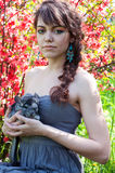 Young girl with chinchilla. Pretty young woman model with bright colorful makeup wearing summer dress, blue earrings, holding her pet chinchilla on her hands Royalty Free Stock Image