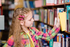 Young girl chooses a book in the library Stock Photography