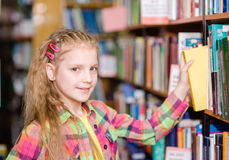Young girl chooses a book in the library Stock Images