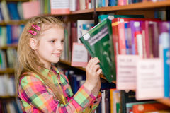 Young girl chooses a book in the library Royalty Free Stock Photography