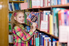 Young girl chooses a book in the library Royalty Free Stock Photos