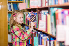 Young girl chooses a book in the library Royalty Free Stock Image