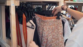 Young girl chooses clothes in second hand, recycling, save the planet, ecology. Young girl chooses clothes in second hand stock video