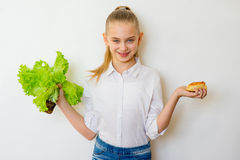 Young girl chooses between a lettuce and baking isolated Stock Image