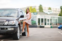 Young girl chooses a used car in a parking lot. Buying a new car. Attractive young woman standing in a car park, choose a car to buy. Used car theme stock photos