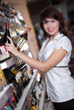 Young girl chooses wine Royalty Free Stock Photography