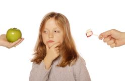 Young girl choosing between an apple and candy Stock Image