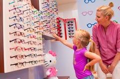 Young girl choosing eyeglasses Stock Photos