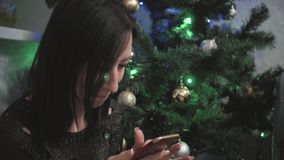 Young girl choosing gifts on smartphone while lie on the floor. Christmas time. stock footage