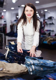 Young girl choosing jeans at store Royalty Free Stock Photo