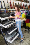 Young girl choosing synthesizer Stock Photography
