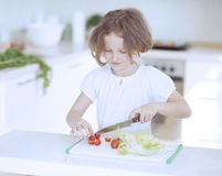 Young girl chopping tomatoes and making a salad in the kitchen Stock Images