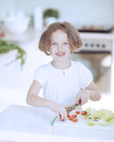 Young girl chopping tomatoes and making a salad in the kitchen Stock Image