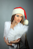 young girl in a Christmas cap and with a fan Stock Photo