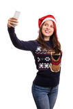 Young girl with a christmas hat taking a selfie isolated on whit Stock Photography