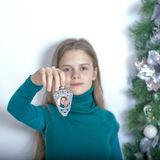Young girl with a Christmas light. Reiterative picture. Royalty Free Stock Photos