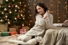 Young girl in christmas lights and decoration, dressed in white sweater and stockings, fir tree on dark wooden background, winter. Holiday concept Royalty Free Stock Photography