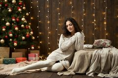 Young girl in christmas lights and decoration, dressed in white sweater and stockings, fir tree on dark wooden background, winter. Holiday concept Royalty Free Stock Photos