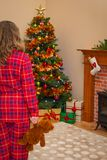 Young girl on Christmas morning. A young girl holding a teddy bear on Christmas morning as she discovers that Santa has been and left lots of gift wrapped Stock Photography