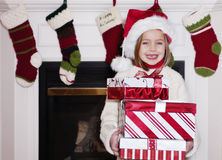 Young Girl with Christmas Presents. A young girl standing in front of the fireplace and stockings with a stack of christmas presents Royalty Free Stock Photo