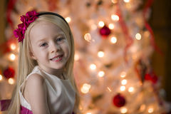 Young girl By Christmas tree lights Royalty Free Stock Photography