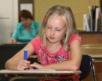 Young girl in class with teacher Stock Photos