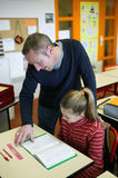Young girl in classroom. Teacher helping girl in classroom Royalty Free Stock Photos