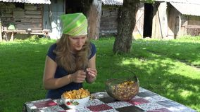 Young girl clean forest chanterelle at table village yard. 4K stock video