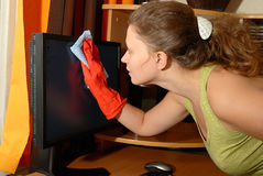 Young girl cleaning. Young Europian girl wiping the dust from LCD monitor royalty free stock image