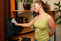 Young girl cleaning. Young Europian girl wiping the dust from LCD monitor royalty free stock photo