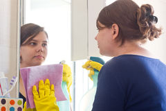 Young girl cleaning in bathroom. Young housewife cleans mirror in bathroom stock photos