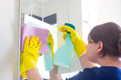 Young girl cleaning in bathroom. Young housewife cleans mirror in bathroom stock images