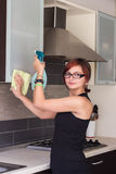 Young girl cleaning furniture in the kitchen stock photography