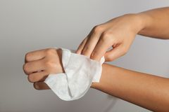 Cleaning hands with wet wipes. Young Girl cleaning hands with wet wipes royalty free stock photography