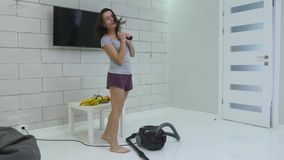 A young girl is cleaning the house using a vacuum cleaner and danced.  stock video footage