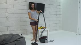 A young girl is cleaning the house using a vacuum cleaner and danced.  stock video