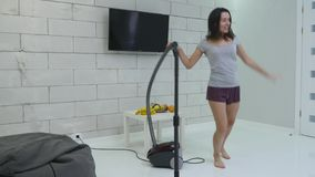 A young girl is cleaning the house using a vacuum cleaner and danced.  stock footage
