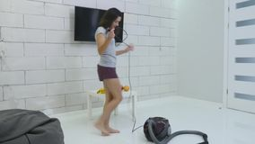 A young girl is cleaning the house using a vacuum cleaner.  stock video footage